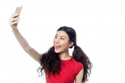 Woman taking selfie using smartphone. Marketing to millennials Seafoam Media