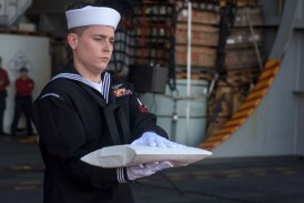 """170715-N-OY799-049 CORAL SEA (July 15, 2017) Yeoman 2nd Class Joseph Hunt, from Beckley, West Virginia, carries the cremains of Julius """"Harry"""" Frey during a burial-at-sea ceremony for Frey and his wife, Jerry, aboard the Navy's forward-deployed aircraft carrier, USS Ronald Reagan (CVN 76), during Talisman Saber 2017. Frey, a WWII veteran, served aboard USS Lexington (CV 2) during the Battle of Coral Sea and his ashes were laid to rest at the coordinates where the ship sank. Talisman Saber is a realistic and challenging exercise that brings service members closer and improves both U.S. and Australia's ability to work bilaterally and multilaterally, and prepares them to be poised to provide security regionally and globally. (U.S. Navy photo by Mass Communication Specialist 2nd Class Kenneth Abbate/Released)"""