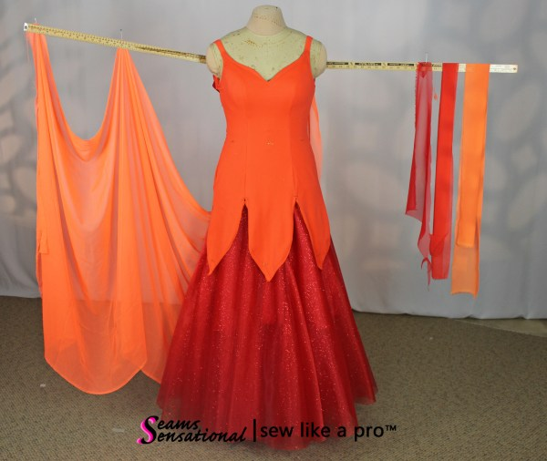 large orange Standard float with multi color drapes on left arm