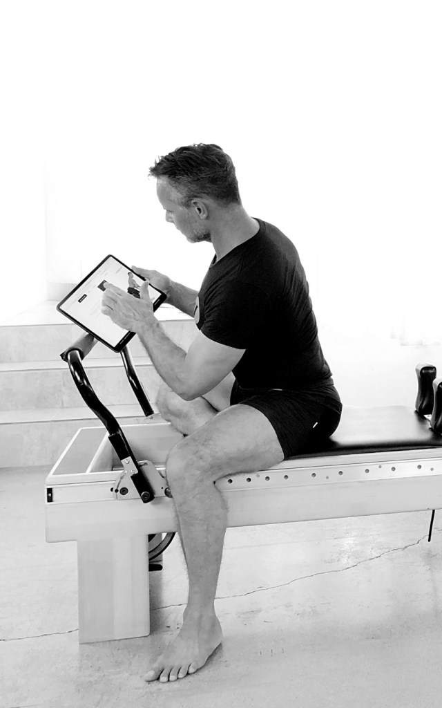 Sean on a pilates machine reading something on a tablet