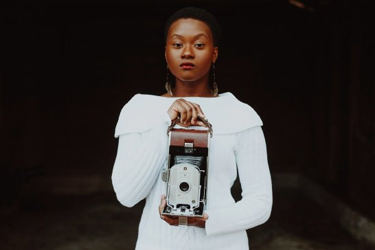 Short haired African American model stares blankly into camera while holding vintage camera
