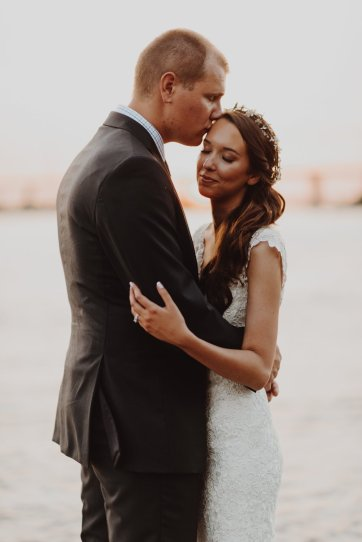 Bride and groom embrace at sunset on the river in downtown Portland Oregon