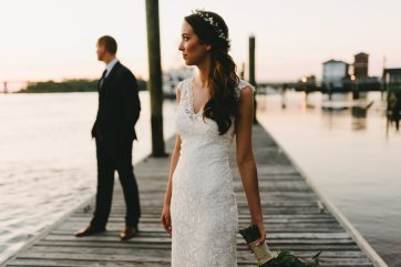 Bride and groom embrace at sunset on a river dock in downtown Portland Oregon