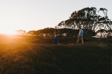 couple wearing casual blue colors embraces during their Oregon coast engagement photos