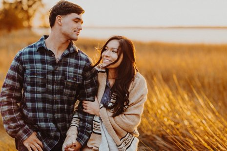Smiling couple walking at sunset during their Oregon coast engagement