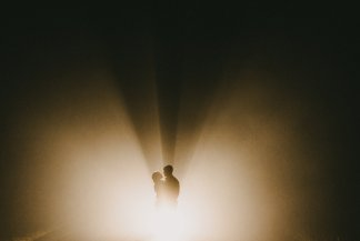 Light rays beam through couple on a foggy night engagement photo in the columbia river gorge