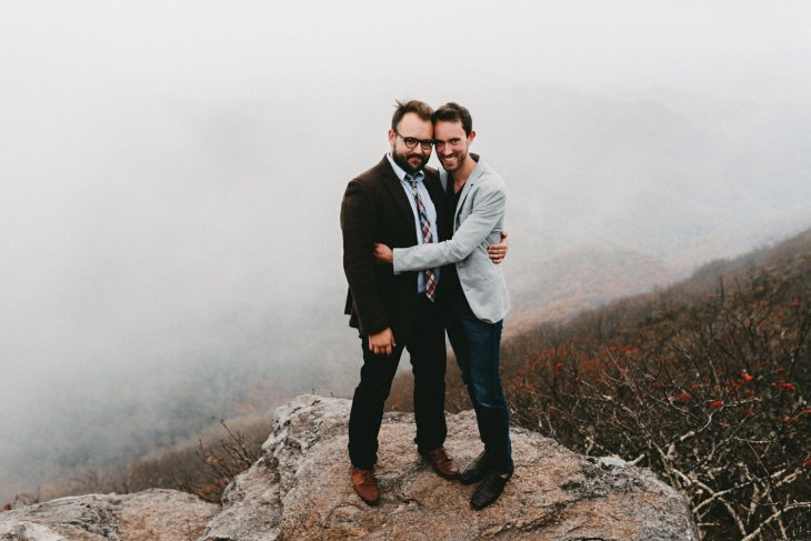 gay couple embraces at Craggy Gardens during their Asheville NC engagement photos