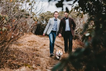 gay couple walks with their corgi Craggy Gardens during their Asheville NC engagement photos