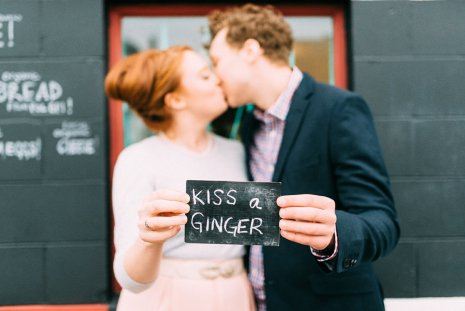 Couple kisses while holding sign during their fifties styled engagement shoot