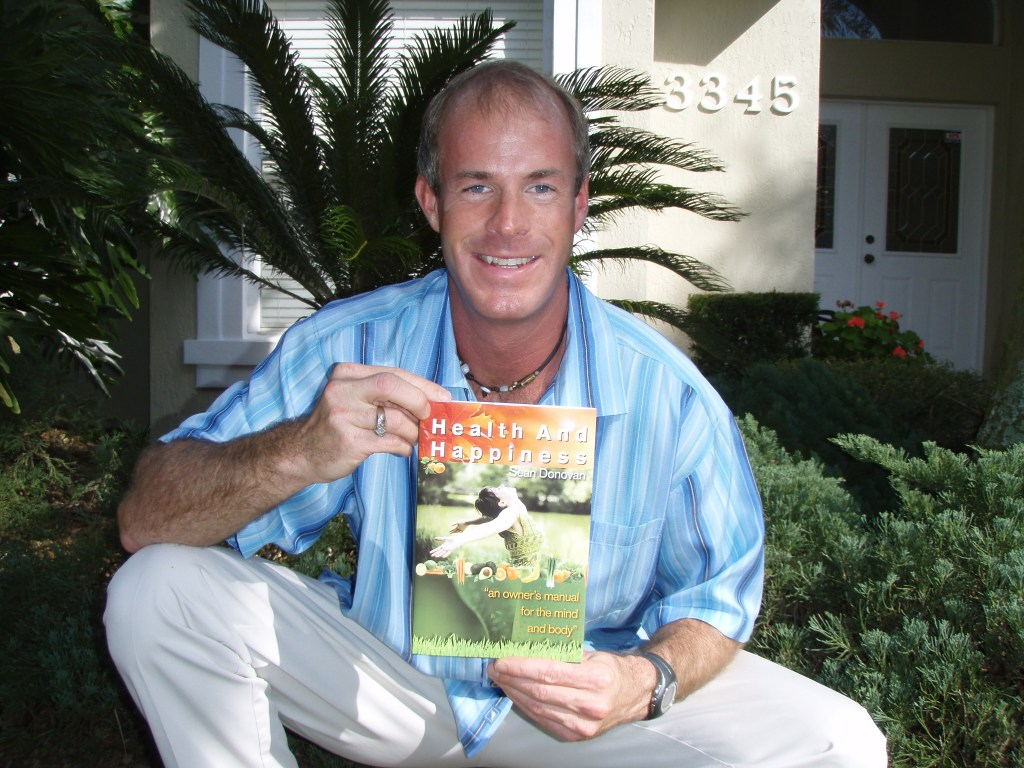 """Sean Donovan holding the first copy of his first book, """"Health and Happiness: an owner's manual for the mind and body"""""""