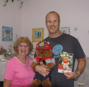 """Elaine Brayton, H.W. Bear, and Sean Donovan pose with a copy of """"The Tales of H.W. Bear"""""""