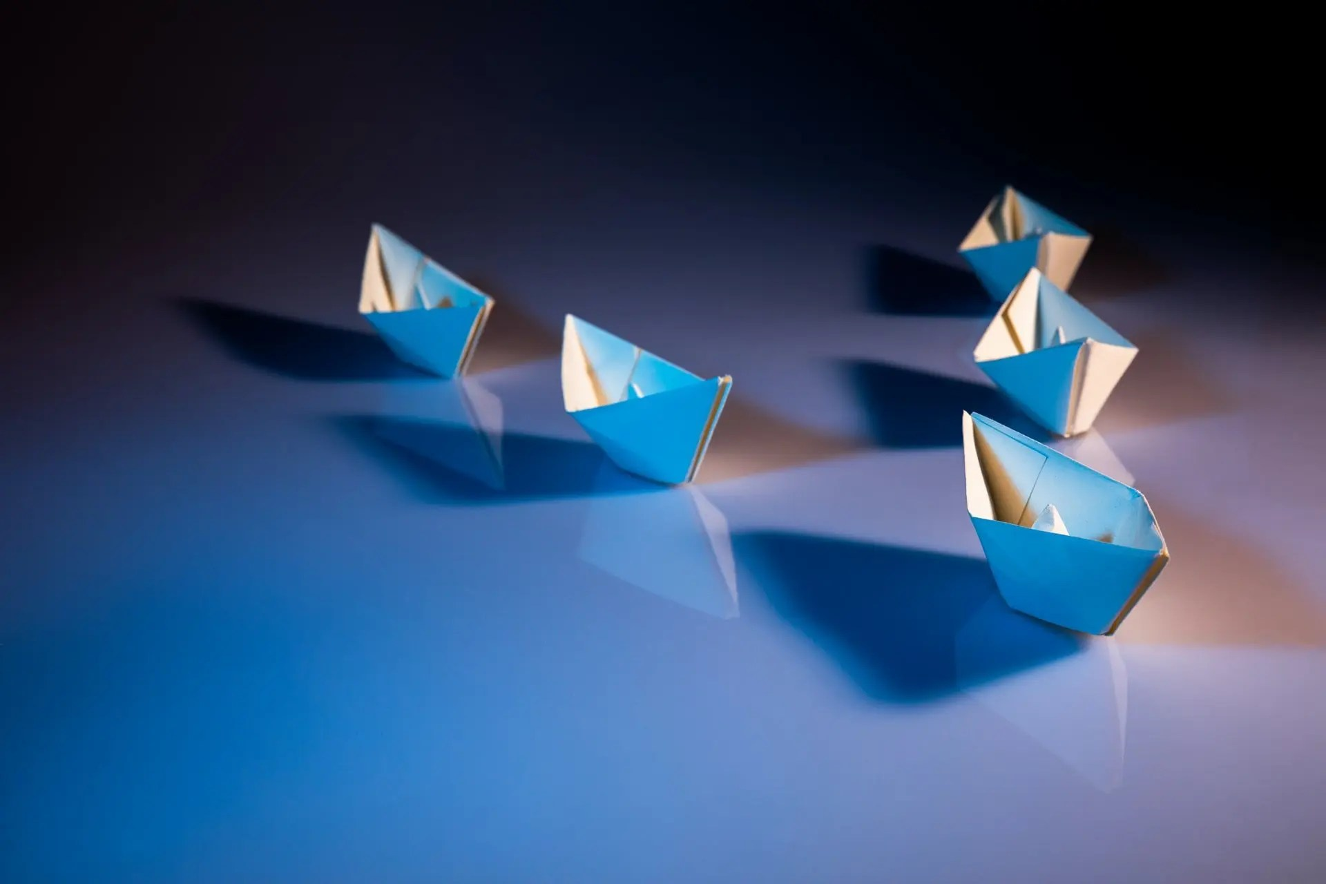 Paper boats lining up behind a leader