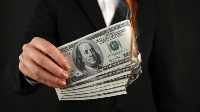Burning hundred dollar bills
