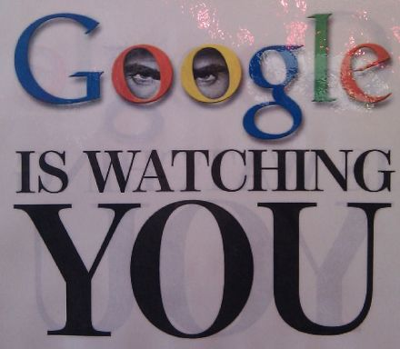 """A photograph of a poster (said to be from one of the Google cafeterias) reading """"GOOGLE IS WATCHING YOU"""" with """"Google"""" being the Google logo. The logo also has two eyes in the Os."""