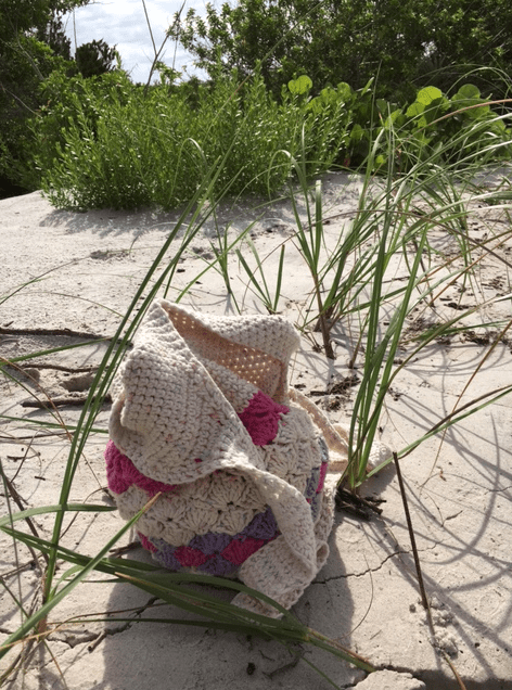 Crocheted bag in sand at beach