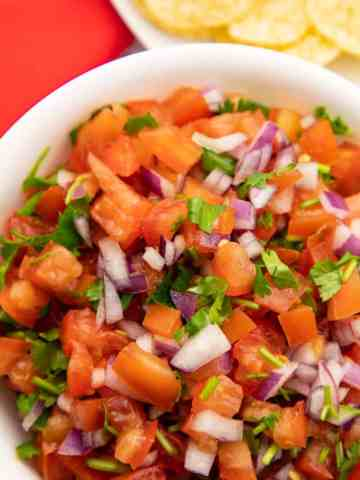 Fresh Tomato Salsa in white bowl with chips