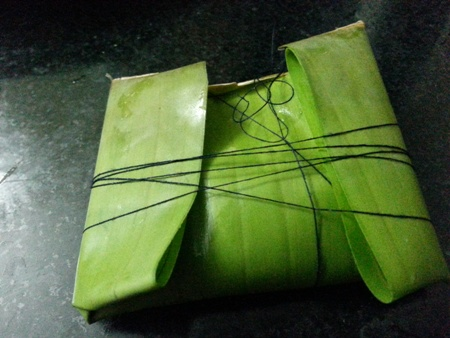 Tie up fish wrapped in banana leaf parcel for Bengali fish recipe