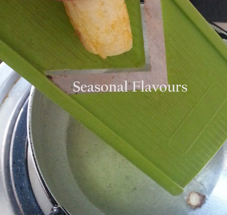 Slice the raw plantain directly into hot oil for Kaya Varuthathu recipe