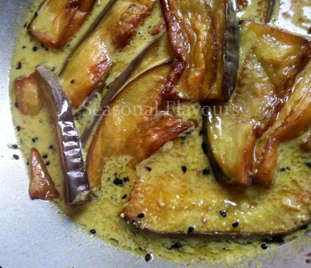 Add fried eggplant slices to gravy for beguner tarkari recipe