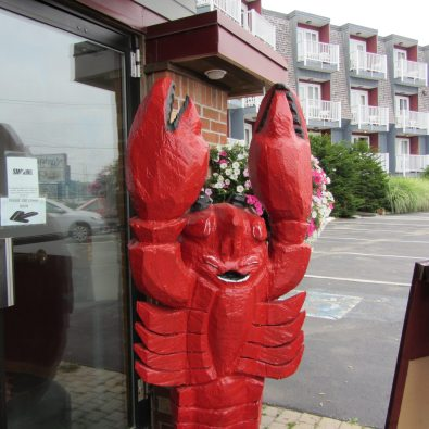 Large red lobster sculpture awaits you at Navigator Inn.
