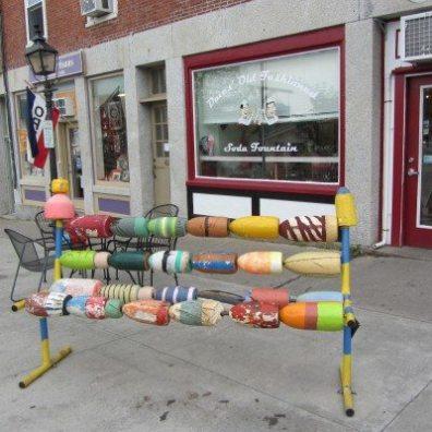 Colorful buoys srung together makes a bench on this sidewalk in town.