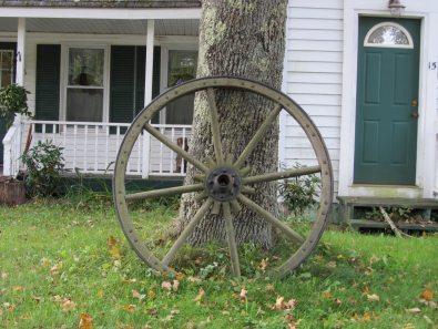 Wagon wheel on front lawn in Washington Village, Washington, Maine