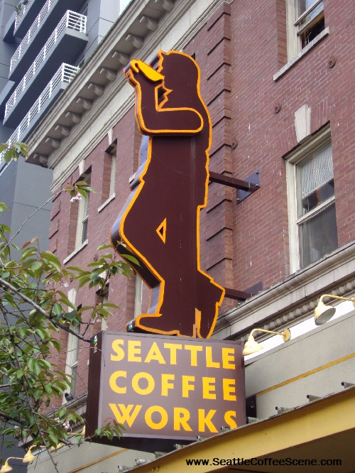 The large Seattle Coffee Works sign enjoys a cup of coffee as it towers over throngs of tourists headed to Pike's Place Market.