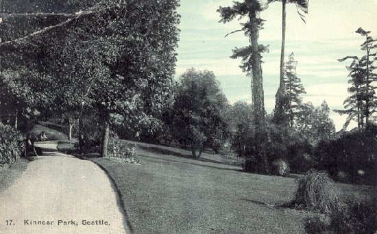 black and white photo of manicured sloping lawn with crushed rock path on the uphill side. Large trees are in the lawn and along the path in the background.