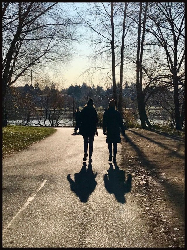 photo of two people walking along shoreline path -- in silhouette with long shadows from late afternoon sun