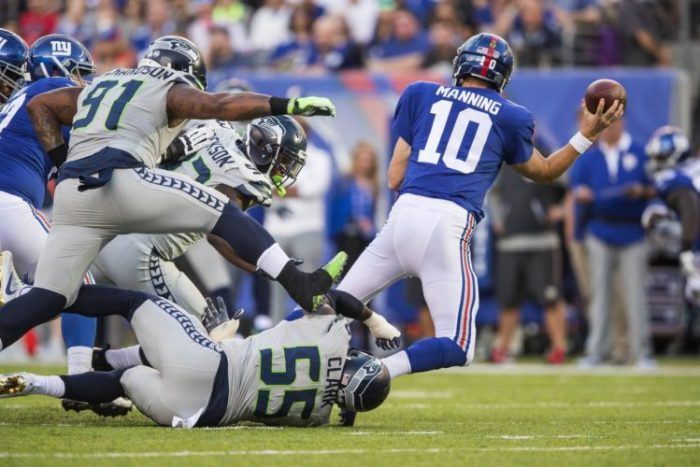 Eli Manning gets taken down as he gets the pass off to avoid the sack. (Dean Rutz / The Seattle Times)