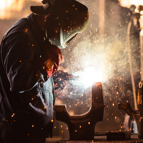 Welder working on heaving machinery
