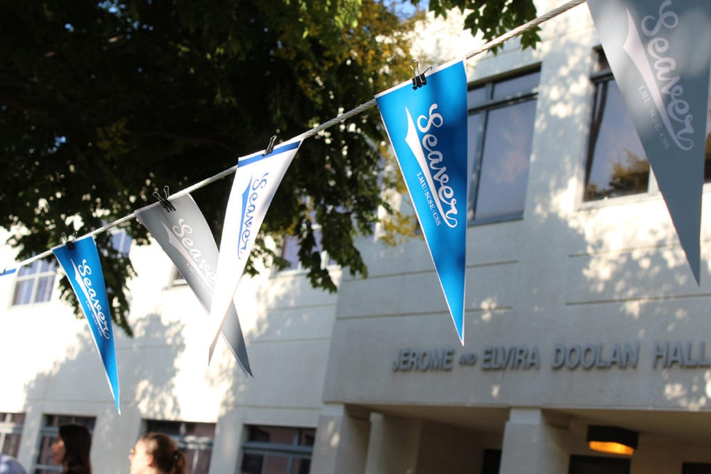 Seaver flags hanging by Doolan Hall