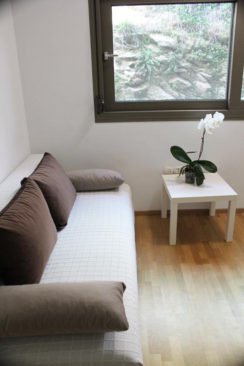 Спальня с видом на скалу, с очень большой двуспальной кроватью и диваном-кроватью