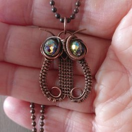 Copper owl pendant held in hand