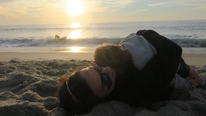 Maman prenant son enfant dans ses bras sur la plage devant le coucher du soleil - img_6288
