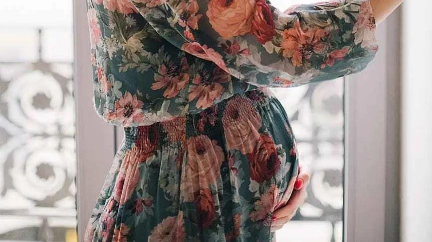 Femme enceinte vêtue d'une robe à fleurs