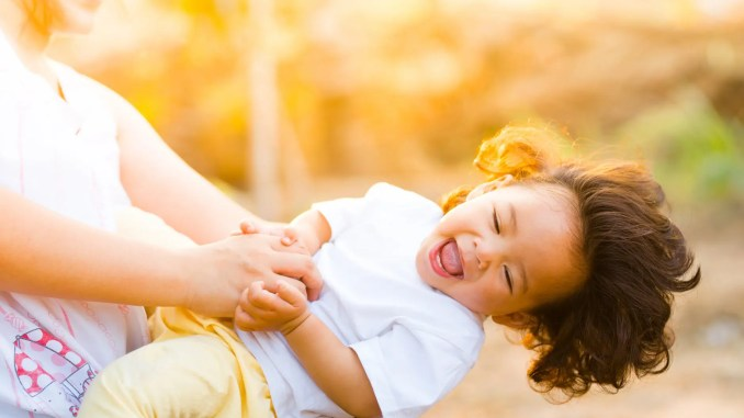 - woman holding baby smiling