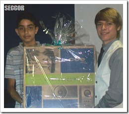 Bruno (esquerda) recebendo o computador de W.Thomas (direita)