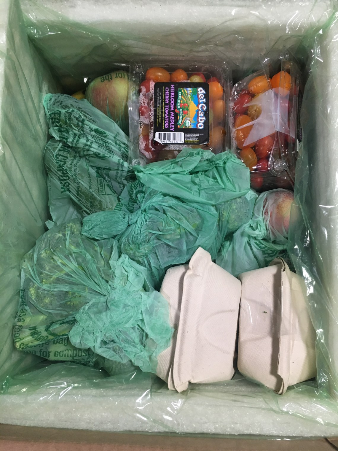 Looking into the just-opened Misfits box we see some cardboard take-out style containers, some veggies like broccoli wrapped in a plastic-type film, loose apples, and grape tomatoes in a plastic clamshell container.