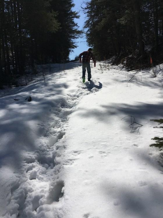 twelve year old boy tromping up an unplowed hill