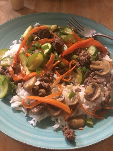 A dish made of ground beef, ribbon carrots, and a variety of sauteed vegetables served over rice.