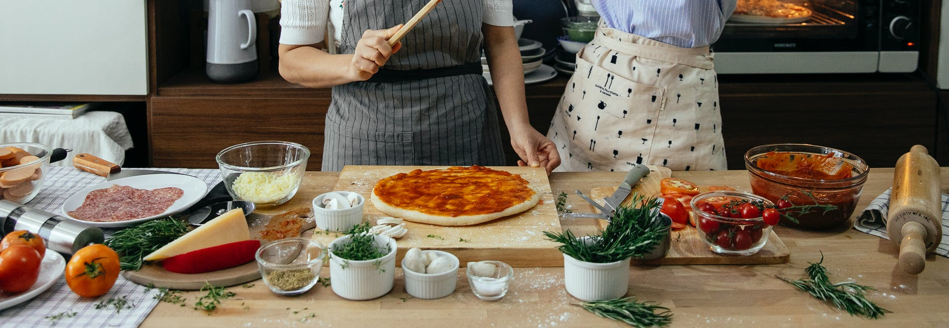 two people spreading red sauce on pizza dough