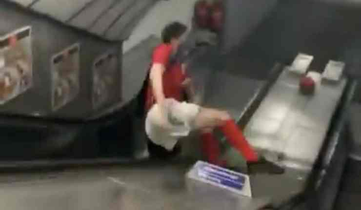 Man slides down tube escalator