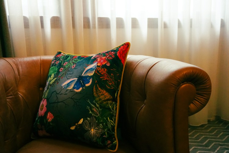 Detail of flower pillow on a brown leather chair
