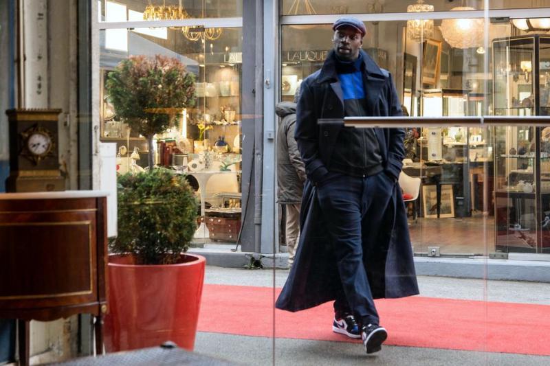 Assane enters Benjamin's shop at the Marché Biron