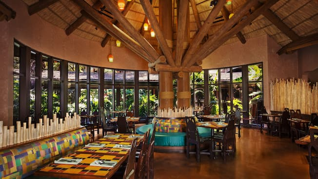 Dining area at Boma Flavors of Africa, featuring a thatched ceiling and windows with a  panoramic garden view