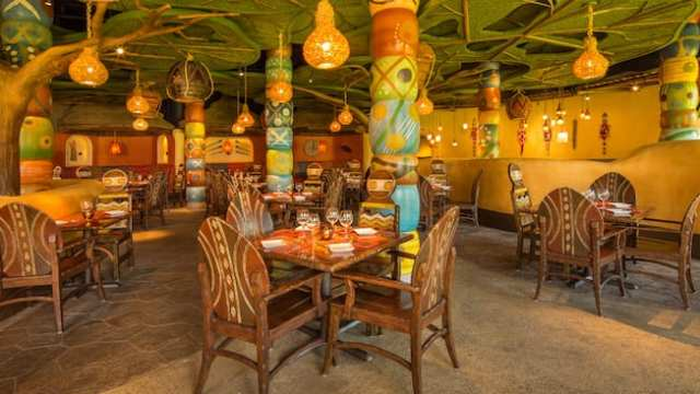 Tribal-design tables under faux tree canopy with hanging lanterns