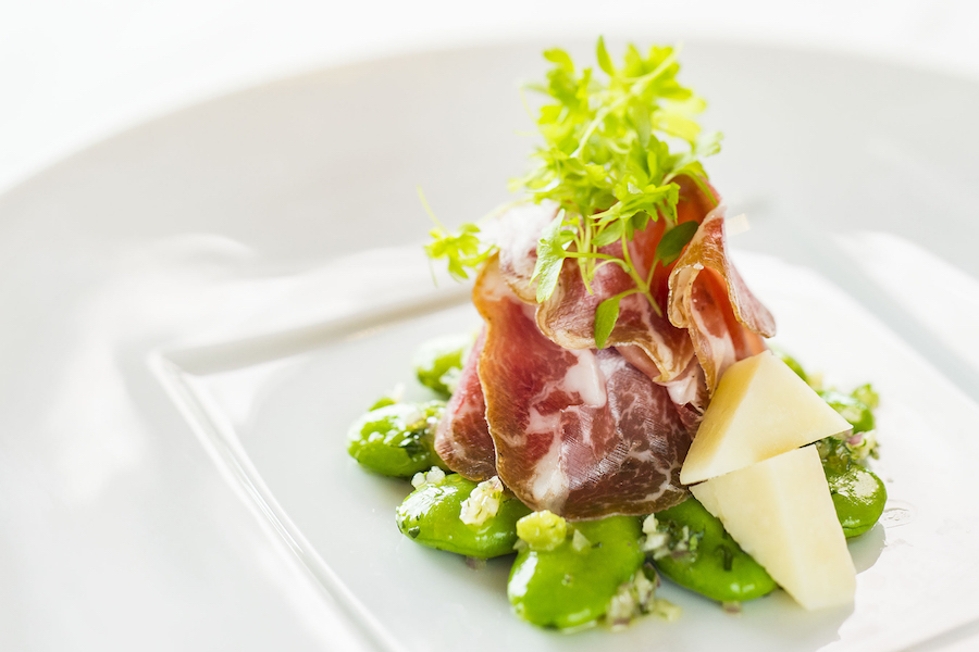 savory coppa (thinly sliced cured pork neck) on dressed fava beans, garnished with sharp Pecurino cheese and micro celery from Palo on Disney Cruise Line Ships