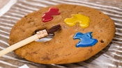 A chocolate chip cookie shaped like an artists palette with three dabs of paint and a paintbrush