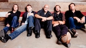 Band members from Sister Hazel kicking their feet out while sitting back against a wood grain wall